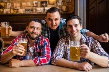 Three young men in casual clothes are smiling and clanging glasses of beer together while sitting in pub