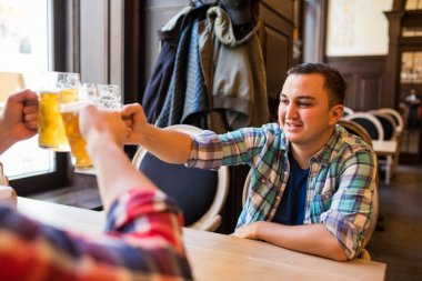 Three young happy men in casual clothes are smiling and clanging glasses of beer together while sitting in pub