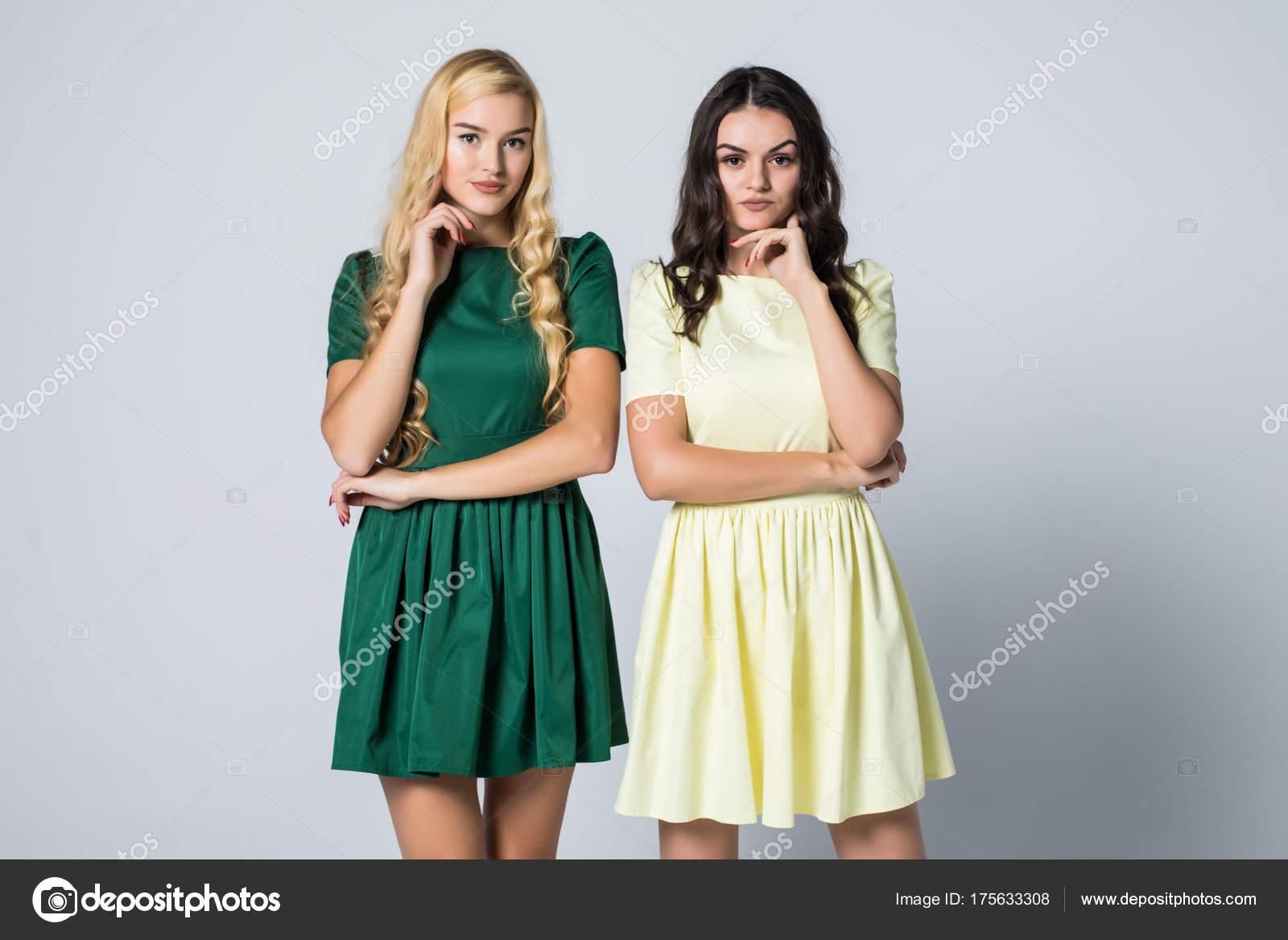 ac2e03a71bbe Πορτρέτο του δύο ελκυστική ξανθιά και μελαχρινή νεαρές γυναίκες σε φορέματα  βλέπουν φωτογραφική μηχανή να ποζάρει