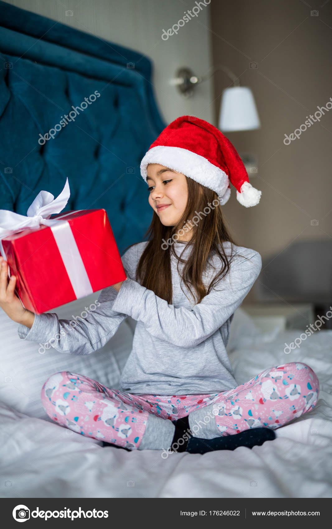 f3cabf807afb9 Charmante fille kid dans le chapeau du père Noël en regardant son coffret  tout en restant assis dans son lit blanc — Image de dan.grytsku.gmail.com