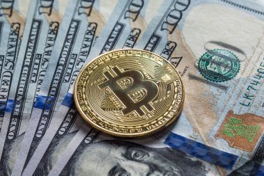 Golden Bitcoins on US dollars background. Electronic money exchange concept. Mining