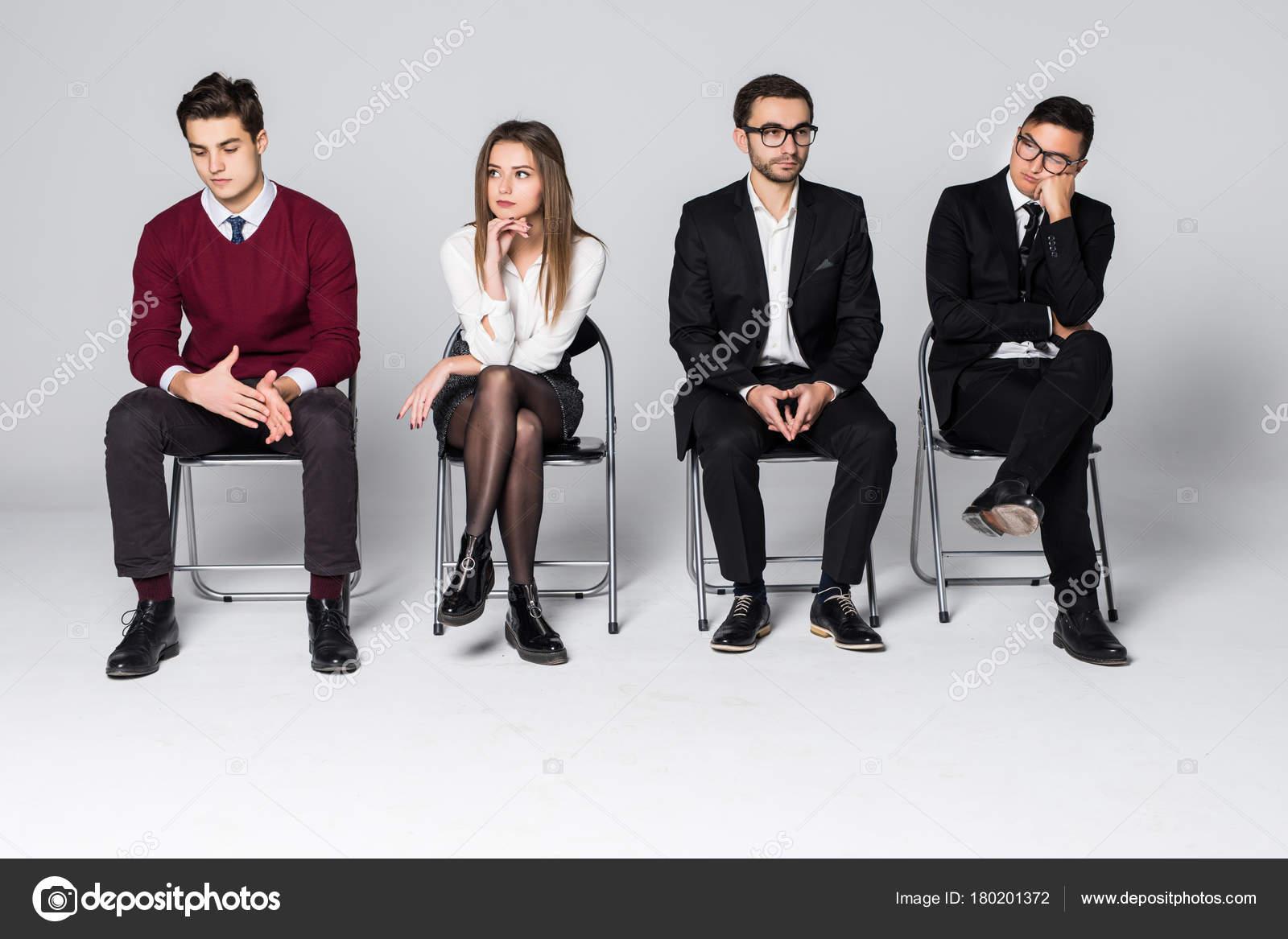 Grupo de personas sentadas en las sillas esperando for Hotel para cuatro personas
