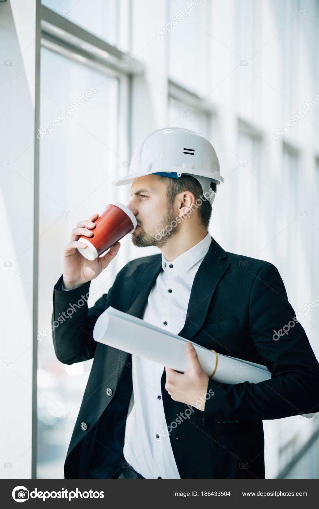 Engineer drink coffee with blueprint in hands before inspection of engineer drink coffee with blueprint in hands before inspection of construction against panoramic windows stock malvernweather Image collections