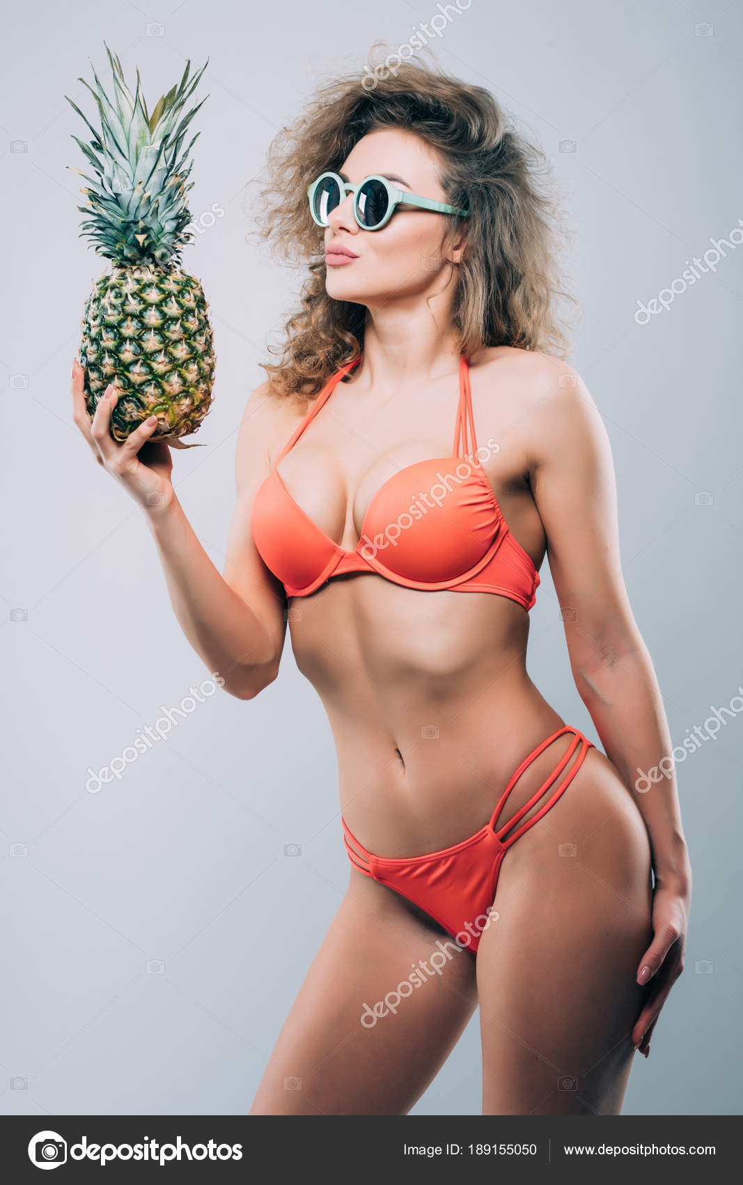 8c57b3dab Young smiling pretty sexy girl holding pineapple and posing isolated on the white  background — Photo by dan.grytsku.gmail.com