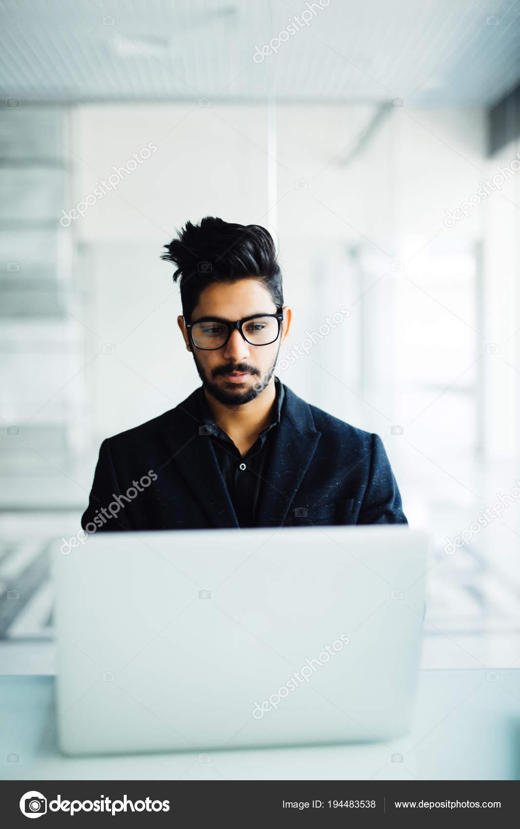 5ef9d60310e67c Indischen Geschäftsmann sitzt an seinem Schreibtisch mit einem Laptop im  Büro — Stockfoto