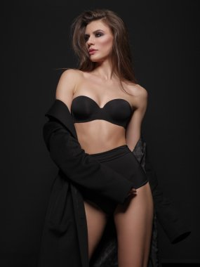 Seductive, beautiful and attractive girl with loose brown hair and sexy gorgeous figure is posing in the black seamless underwear on the dark background in the studio