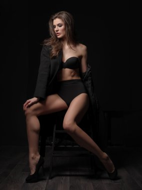 Seductive, beautiful and attractive young female model with loose brown hair, sexy gorgeous figure and long legs in the black seamless underwear and wool coat is posing on the chair in the studio