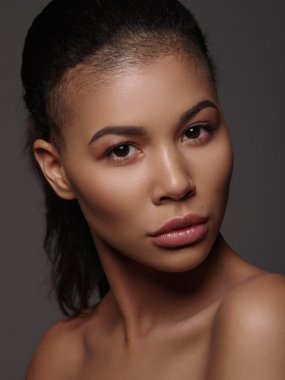 Fashion portrait of an extraordinary beautiful african american young woman with perfect smooth golden skin, full lips and shaved haircut, studio shoot, dark background