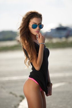 Beautiful seductive young girl of modeling appearance is posing in underwear on the runway wearing aviator sunglasses, fashion outdoor urban  photoshoot