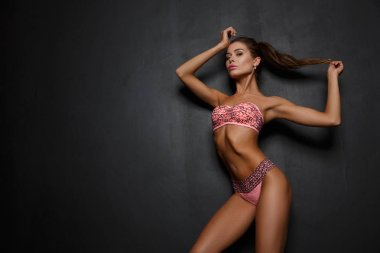 Sexy seductive girl in pink underwear (lingerie) with slim athletic tanned figure is posing in the studio, dark background
