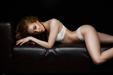 Seductive, sexy and beautiful young woman with makeup in white underwear is lying and posing stretched on the black leather couch in a feline pose, erotic romantic evening, dark studio background