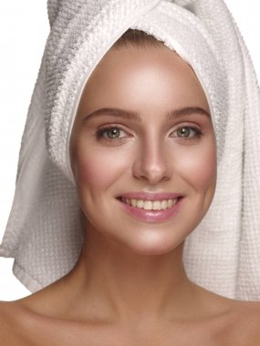Portrait of a young girl with pure, healthy, smooth and natural glowing skin without any makeup, who is doing daily skincare after the shower with the towel on her head, white isolated background