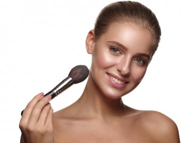 Portrait of a girl with pure and healthy glowing smooth skin, who is applying daily makeup on her face using a brush in her hand, studio shoot, white isolated background