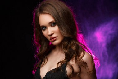 Studio portrait of a young confident and beautiful woman with long wavy hair and expressive makeup on the black background, backlight