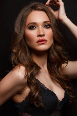 Studio portrait of a young attractive and beautiful woman with long wavy hair and expressive makeup on the black background