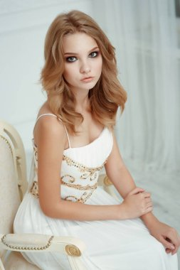 Smartly dressed charming young beautiful girl (teenager) with frail figure and blond wavy hair wearing white evening dress embroidered with sequins is posing in the light interior studio room