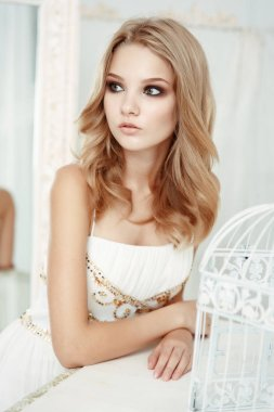 Smartly dressed pretty and elegant young girl (teenager) with frail figure and blond wavy hair wearing white evening dress embroidered with sequins is posing in the light interior studio room