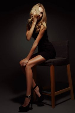 Sexy and beautiful young blonde woman with slim figure, long  seductive legs and tanned skin is sitting in the black little dress and high heels on the chair in the studio, dark wall on the background