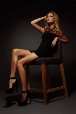 Sexy and beautiful young blonde model with slim body, long  seductive legs and tanned skin is posing in the black little dress and high heels in the studio on the chair, dark wall on the background