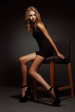 Sexy and beautiful young blonde girl with slim figure, long  seductive legs and tanned skin is posing in the black little dress and high heels in the studio on the chair, dark wall on the background