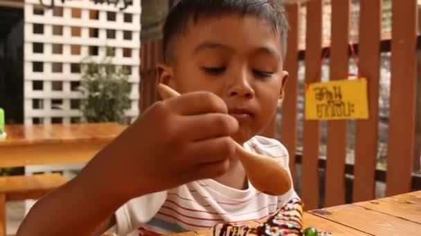 süßer kleiner Junge isst Süßfleisch