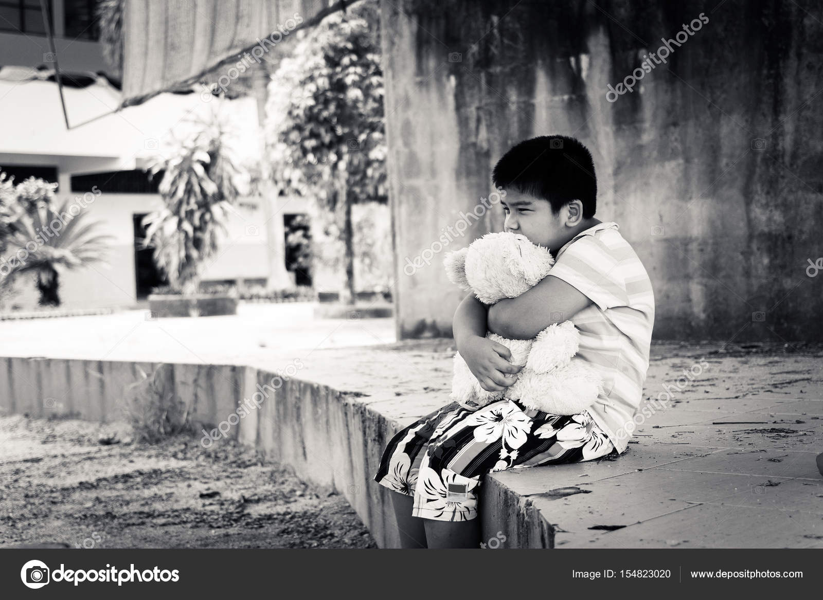 Cute asian boy crying alone in the park black and white tone photo by
