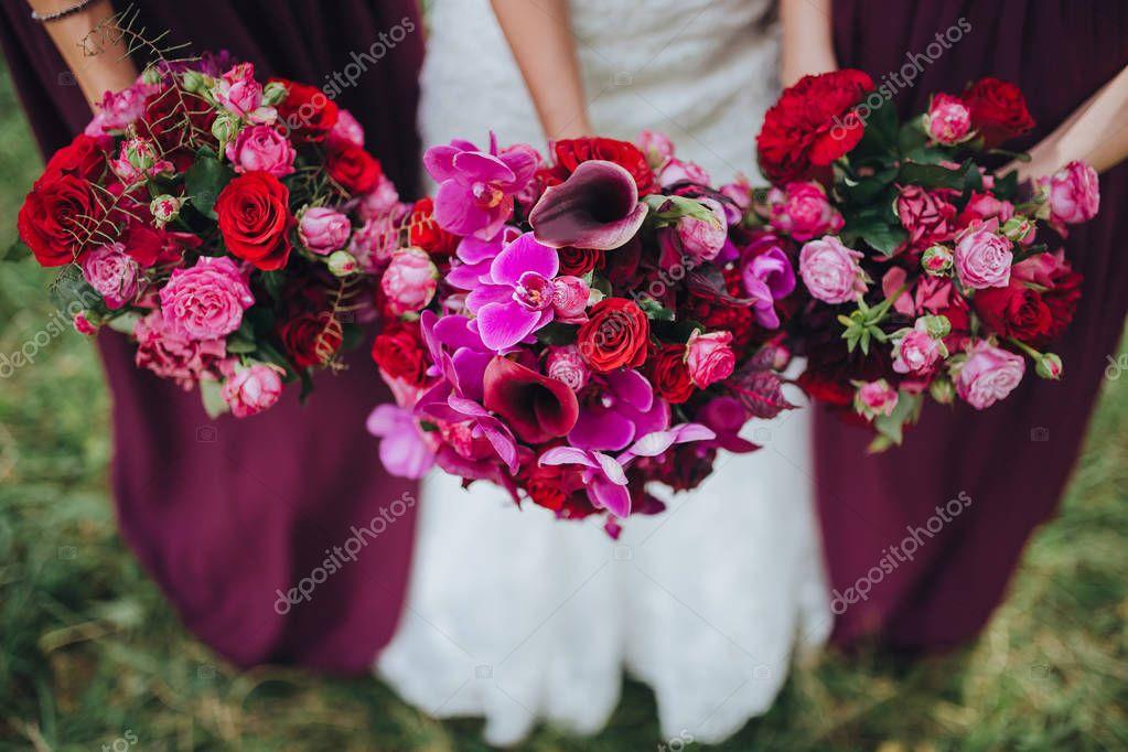 Three wedding bouquets in hands