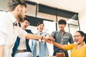 Mnohonárodnostní různorodá skupina happy kolegy spojili ruce. Kreativní tým, neformální obchodní spolupracovník nebo vysokoškoláci v projektové setkání v moderní kanceláři. Při spuštění nebo týmovou práci koncepce