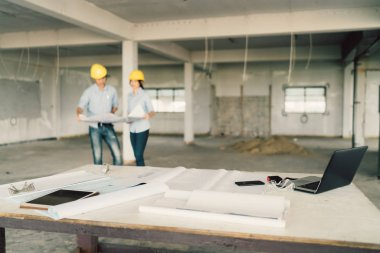 Blueprint, laptop computer, and industrial tools at construction site with two engineers or architects working together in blur background. Industry, building architecture, or teamwork concept