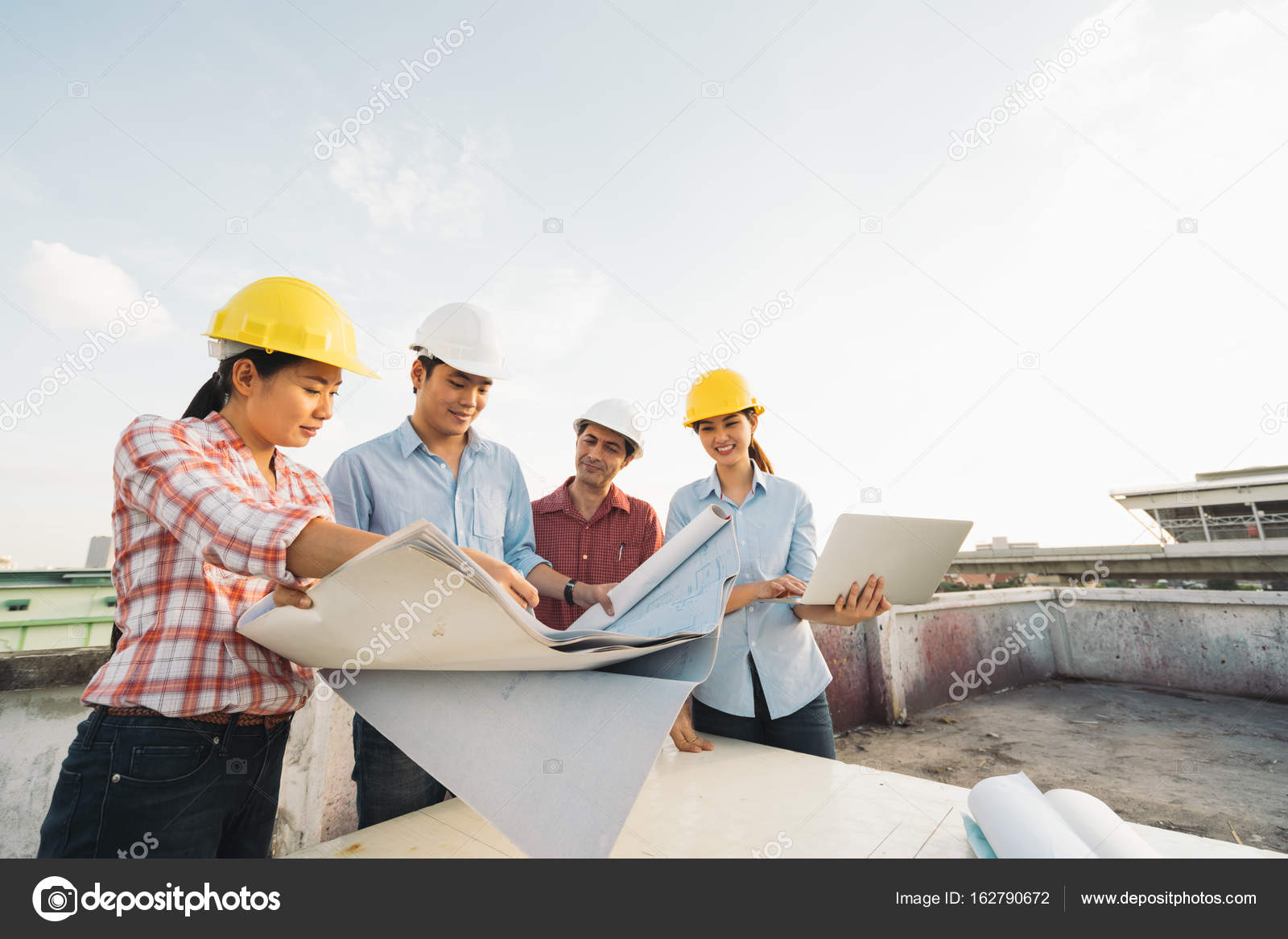 Multiethnic diverse group of engineers or business partners at multiethnic diverse group of engineers or business partners at construction site working together on buildings blueprint architect industry or teamwork malvernweather Images
