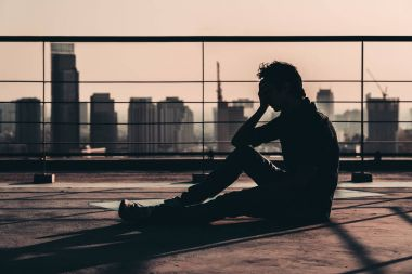 Silhouette of sad depressed Asian man lost hope and cry, sit on building rooftop at sunset, dark mood tone. Concept of major depressive disorder, friend zone, unemployment, stress emotion or paranoid