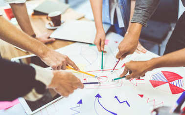 Creative idea teamwork concept. Group of multiethnic diverse team, business partner, or college students in project meeting at modern office. Five people pointing at lightbulb drawings