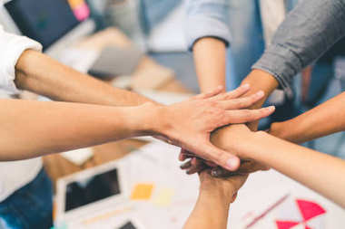 Business partners teamwork or friendship concept. Multiethnic diverse group of colleagues join hands together. Creative team, coworkers, or college students in project meeting at modern office.