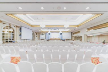Blurred, defocused background of modern conference room. Company business meeting, convention center, financial economic forum, or organization event concept