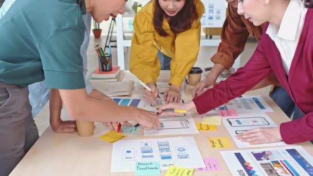 Junge asiatische Unternehmen kreative Team arbeiten zusammen, mobile Anwendung Software-Design-Projekt. Brainstorming-Treffen, Internettechnologie, Teamwork-Konzept für Büromitarbeiter. 4K Neigung nach hinten Dolly Schuss