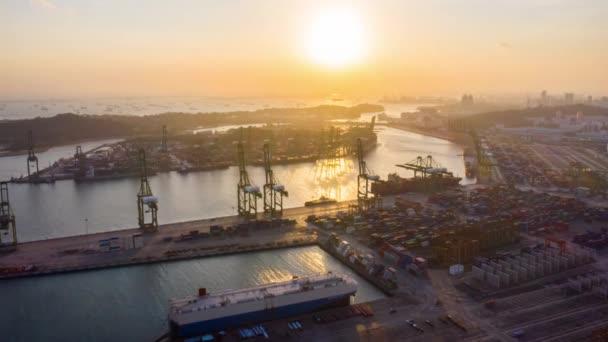 Hyperlapse időeltolódás Szingapúr ipari tengeri kikötő rakomány konténer, szállítóhajó, daru, sziluett naplemente. Logisztikai ipar, áruszállítás. Drónantenna magasszögű nézete