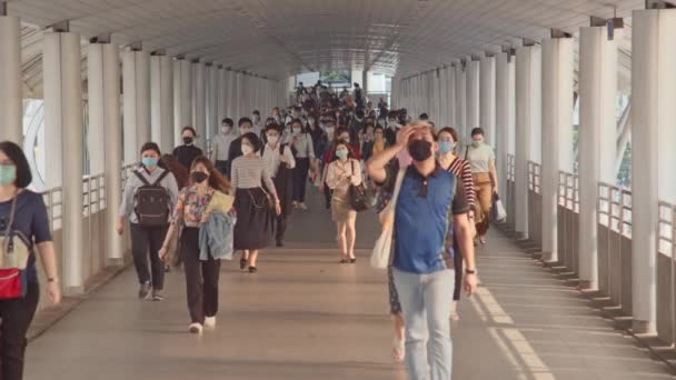 Bangkok, Thailand - Apr 7, 2020: Crowded Asian people wear face mask walking in pedestrian walkway. Coronavirus disease Covid-19 pandemic outbreak, city life, or air pollution concept. 4K slow motion