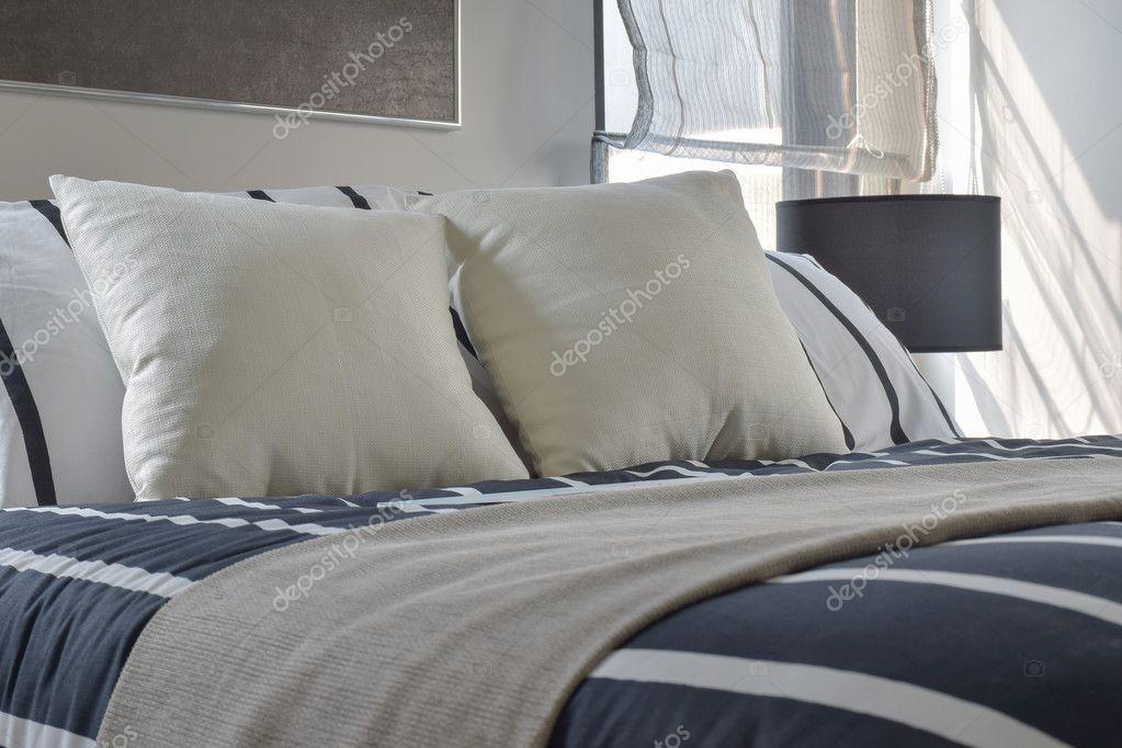 Naturel en gestreepte kussens op bed met diep blauwe gestreepte ...