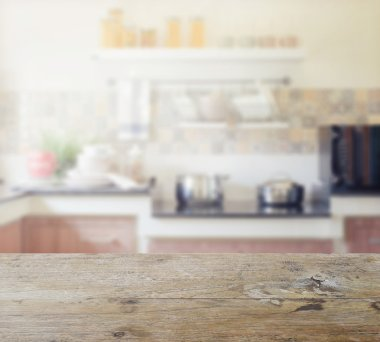 wooden table top with blur of modern kitchen interior