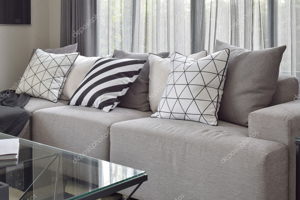Licht grijze bank met varieert patroon kussens in moderne zithoek