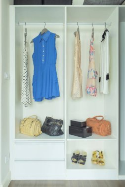 Dresses, bags and shoes in white wardrobe