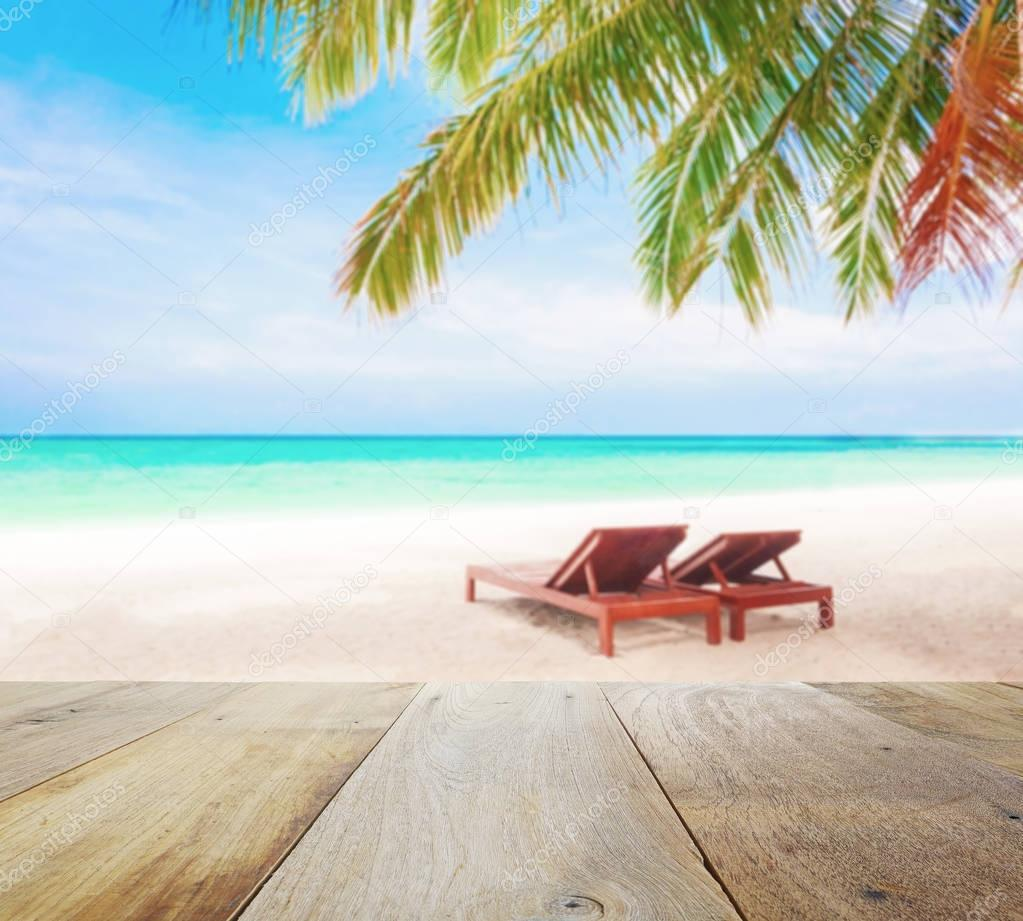wood table top on blur beach background with beach chairs under coconut tree