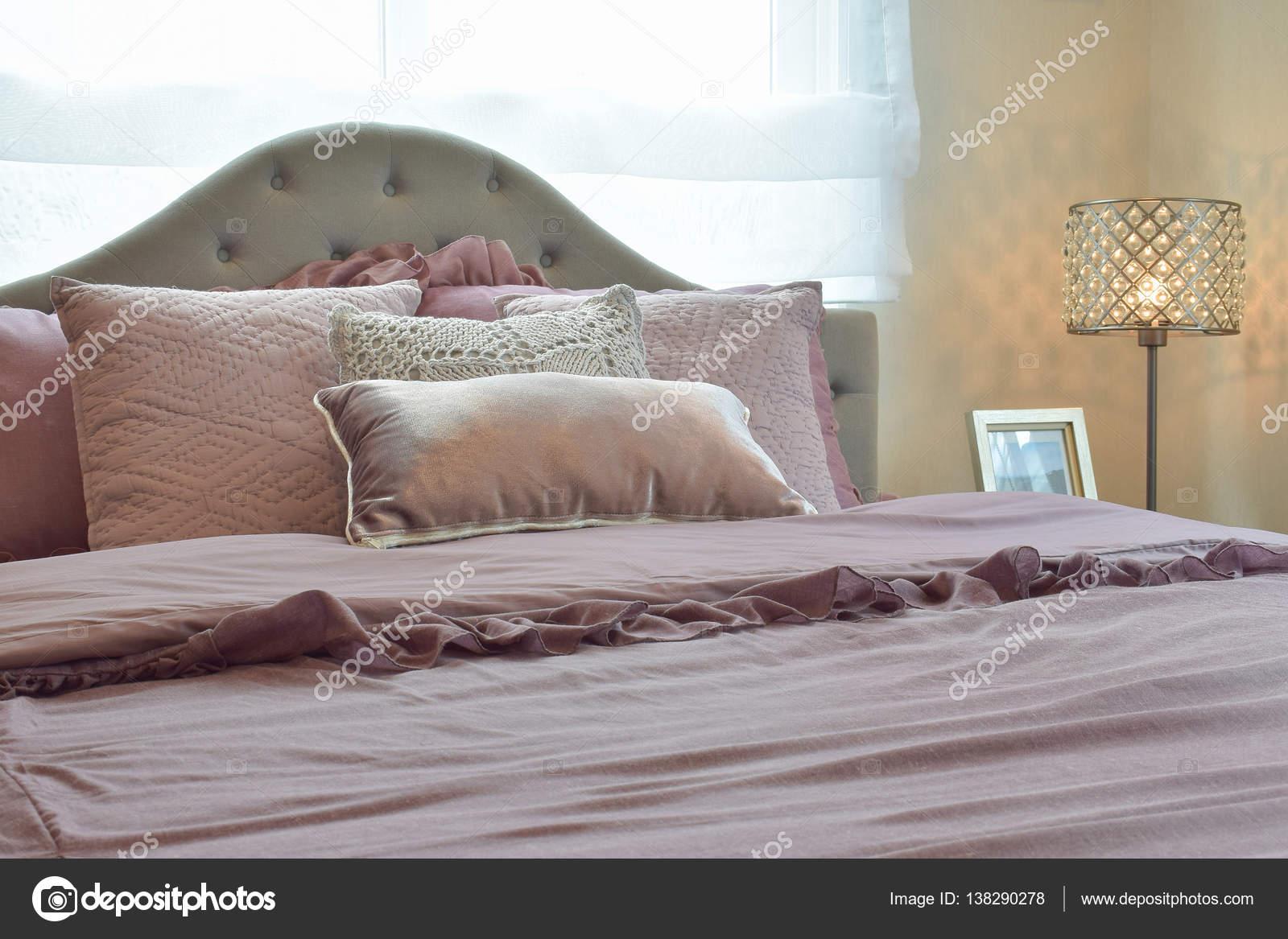 gezellige en klassieke slaapkamer interieur met kussens en leeslamp op nachtkastje stockfoto