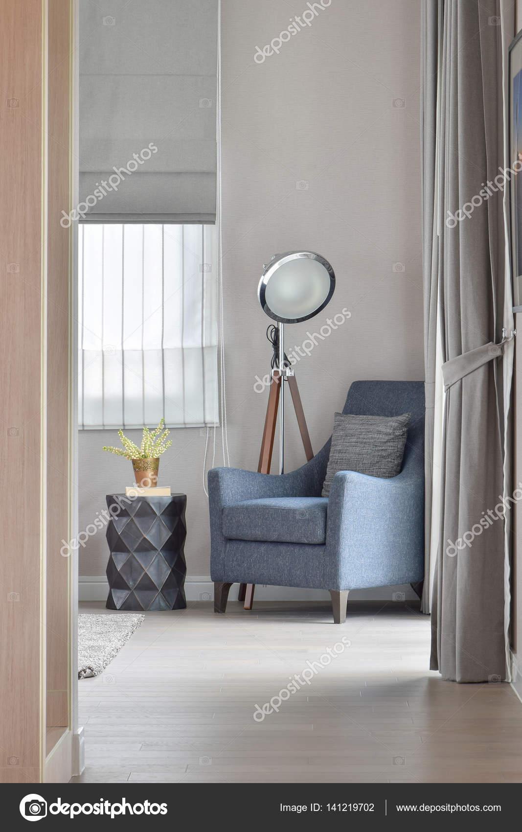 Diepblauwe fauteuil met stijlvolle staande lamp in de hoek van de ...