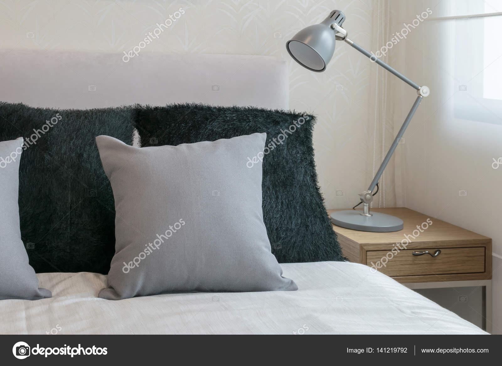 arredamento camera da letto con cuscini grigi sul letto bianco e ...