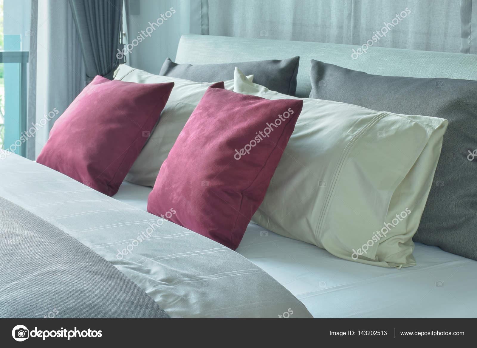 Almohadas de terciopelo rojo con cojines blancos y grises en cama en ...