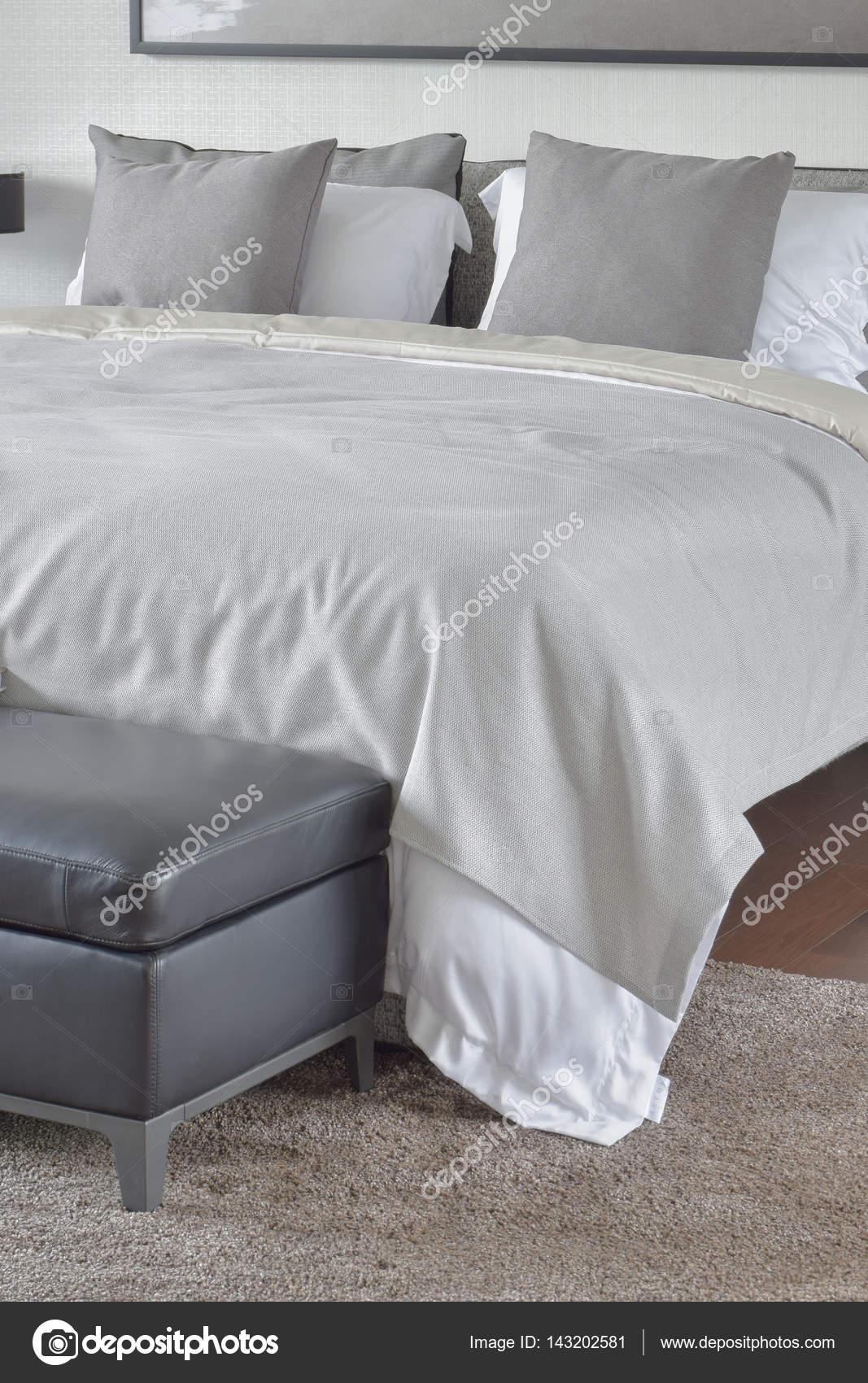 Manta beige en cama con otomana de cuero negro — Foto de stock ...