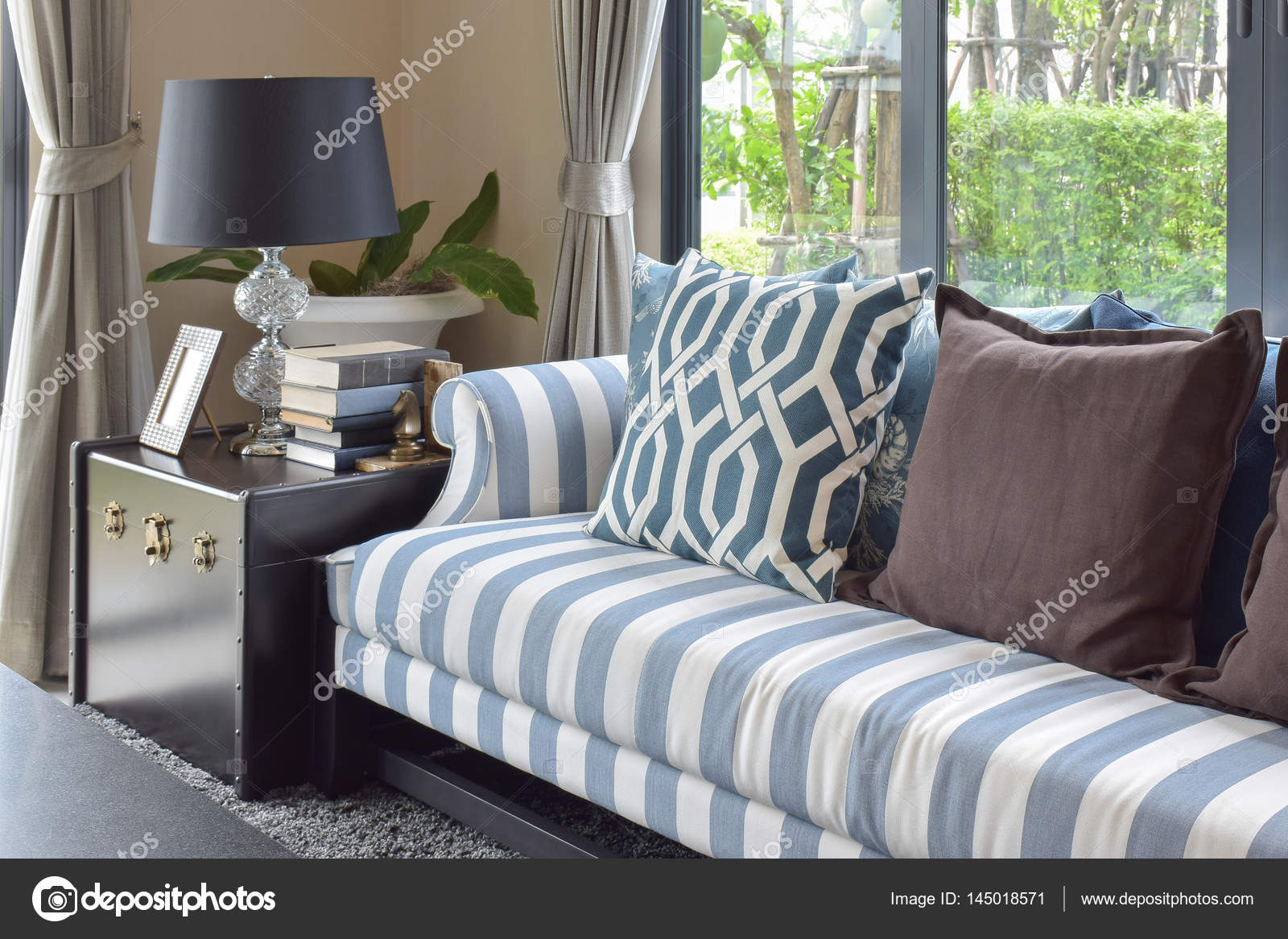 Blue pattern pillows on striped sofa with black lamp in living room ...