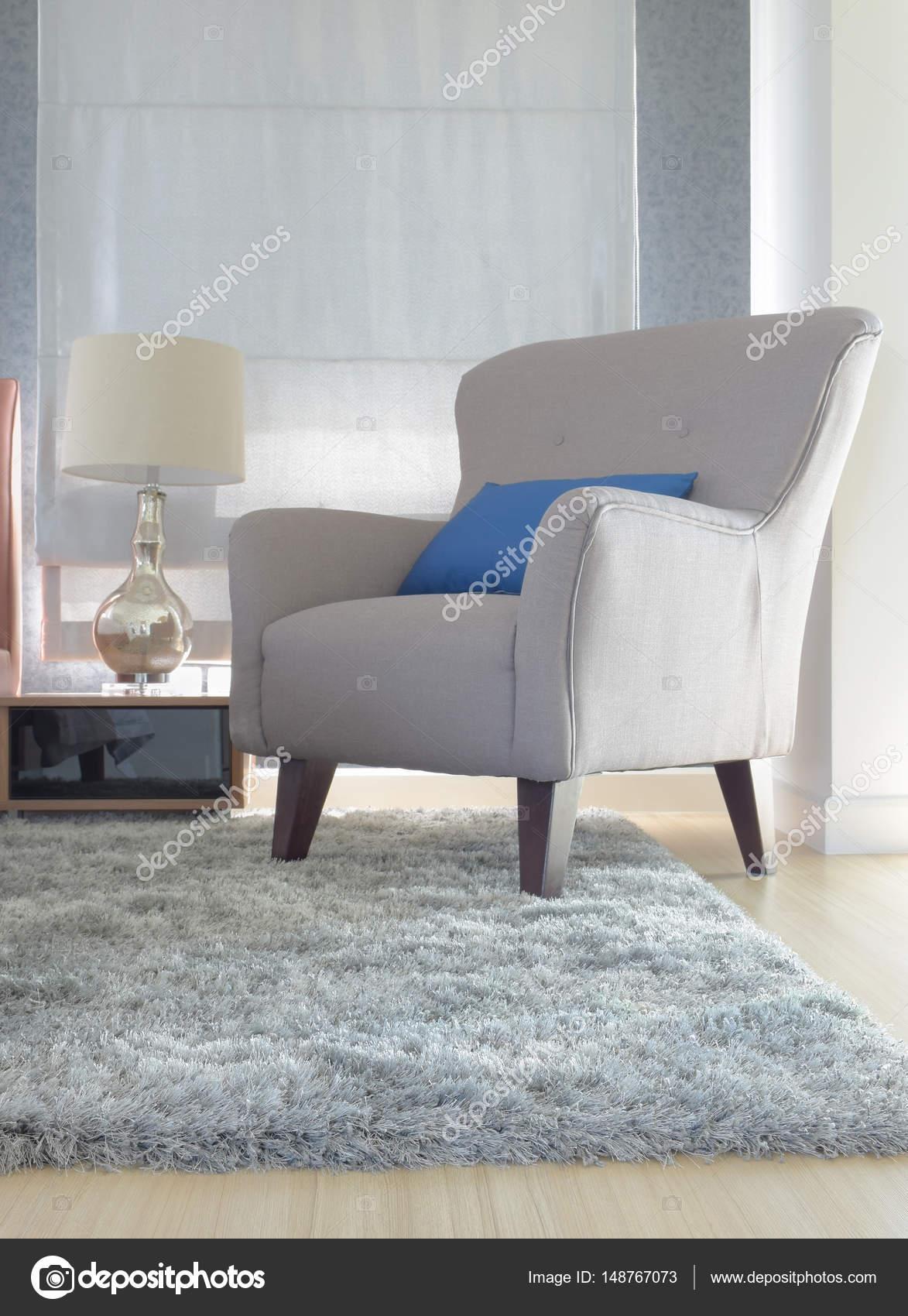 Grijze bekleding fauteuil met blauw kussen in moderne interieur ...
