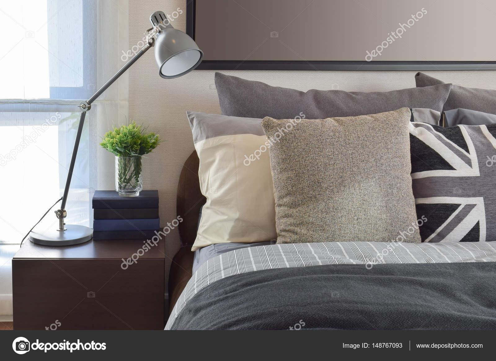 Comò Camera Da Letto Moderna : Camera da letto moderna con cuscino grigio e la lampada sul